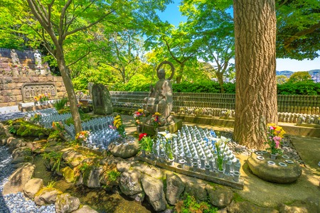 Bronze buddha statue and lots little Jizo Statues in Hase-dera, Kamakura, Japan. Hasedera is one of the largest Buddhist temples in the city. Japanese culture concept Stock Photo