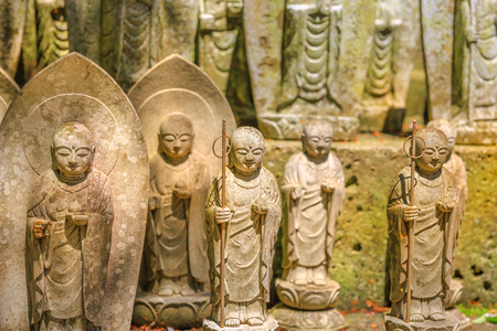 A lots of stone Jizo Bodhisattva statues background. Hase-dera in Kamakura, Japan. Hasedera is one of the largest Buddhist temples in the city within a pilgrimage circuit of the goddess Benzaiten. Stock Photo