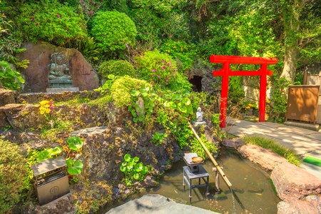 Kamakura, Japan - April 23, 2017: Japanese bamboo fountain in Hase-Dera garden or Hase-kannon and Torii gate or Shinto gate in front of Benten-kutsu cave entrance. Hasedera Temple is popular landmark Editorial