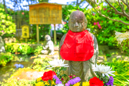 Close up of stone Jizo statue with red scarf on his neck on blurred background. Hase-dera in Kamakura, Japan. Hasedera is one of the largest Buddhist temples in the city. Japanese culture concept Stock Photo