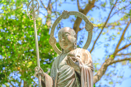 Close up of stone Jizo statue on blurred background in the blue sky. Hase-dera in Kamakura, Japan. Hasedera is one of the largest Buddhist temples in the city. Japanese culture concept