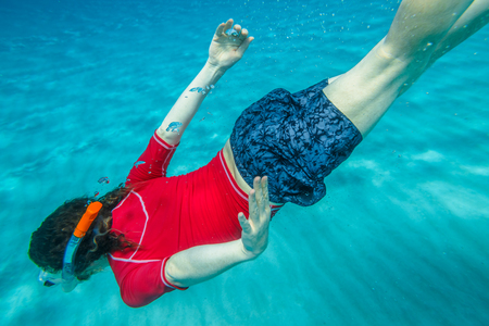 Male apnea swims in crystal sea. Underwater background of a man snorkeling and doing free diving. Watersport activity in summer vacations. Tropical destination holidays concept.