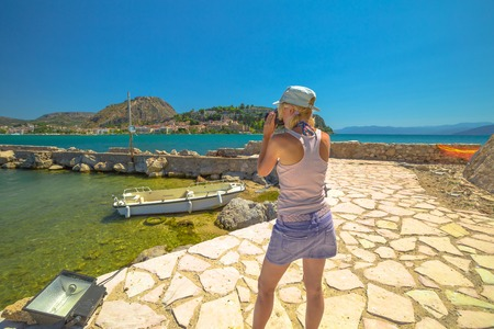 Travel woman photographer takes shot of Nafplio, famous seaside town of Peloponnese, Greece from Fortaleza de Bourtzi. Female photographing Palamidi Fortress a top of mountain. Travel vacation concept