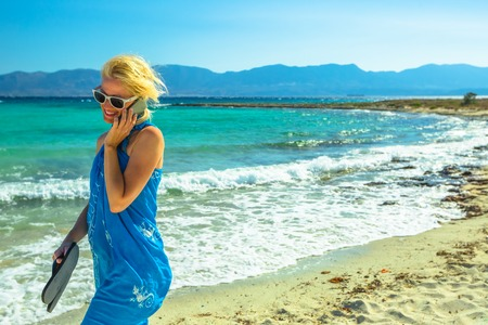 Happy woman talking on a smartphone walking on the beach. Beach woman wearing an blue sarong, sunglasses and holding sea slippers enjoying. Turquoise sea of famous Elafonisos island, Greece, behind.