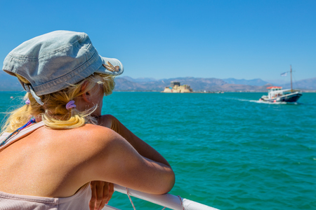 Caucasian female on boat looking to Fortaleza de Bourtzi, symbol of Nafplio, famous seaside town of Peloponnese in Greece, Europe. Woman boat trip enjoying the sea. Summer travel vacation concept. Stock Photo