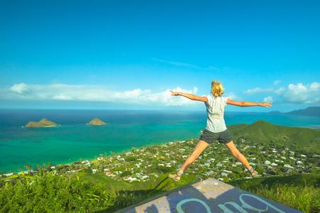 Lanikai Pillbox Hike. Hawaiian hiking enjoying. Joyful carefree hiker jumping. Happy woman celebrates one of most spectacular Oahu hiking trails in Hawaii over Lanikai Beach and Mokulua Islands. Stock Photo