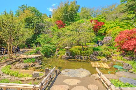 Kamakura, Japan - April 23, 2017: smaller flowering garden with a pond near the Kannon-do hall in a sunny day with blue sky. Hase-dera Temple in Kanagawa Prefecture, Kamakura. Spring season.