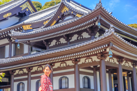 Kamakura, Japan - April 23, 2017: smiling young woman wearing japanese kimono at Kannon-do or Main hall of Hase-dera Temple in Kamakura. Japanese culture and lifestyle. Spring season. Editorial