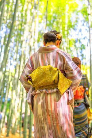 Unidentifiable woman wearing Japanese kimono walking in bamboo grove of Take-dera or Hokoku-ji Temple at sunset light in Kamakura, Japan. Japanese culture and lifestyle. Hanami in spring season.