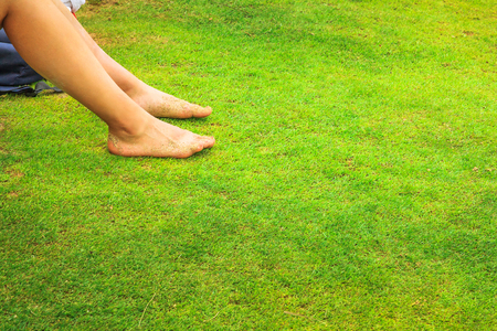 Woman with bare legs relaxing in grass of a park background during summer sunny day. Holidays picnic in the green nature. Leisure and lifestyle concept. Copy space.