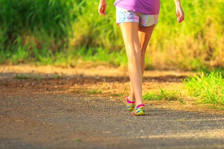 Healthy lifestyle woman in colorful shoes walking after running in the park at sunset. Fit woman runner jogging on a country road. Outdoors and healthy life concept. Stock Photo