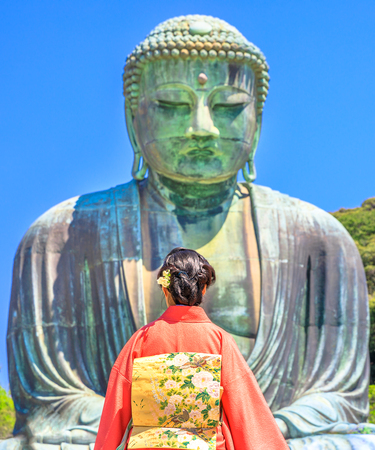 Unidentifiable woman wearing Japanese kimono looking Great Buddha or Daibutsu. The monumental Buddha Vairocana in Kotoku-in Temple is one of main attractions in Kamakura, Japan.Hanami in spring season Stock Photo