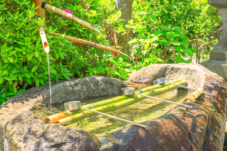 Japanese Buddhist bamboo fountain with three ladles at a Buddhist temple. Hase-dera in Kamakura, Japan. Japanese culture concept. Japanese purification ritual.
