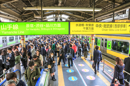 Tokyo, Japan - April 17, 2017: commuters on the sidewalk waiting for the train at rush hour in Shinjuku Station, Tokyos main station. Yamanote Line loop and Sobu Line local signboard.