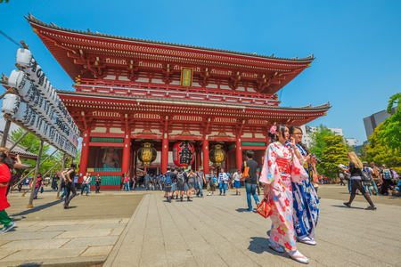 Tokyo, Japan - April 19, 2017: young women in traditional japanese kimonos coming out of the Hozomon, Treasure-House Gate, theentrance of Buddhist Temple Senso-ji, Asakusa, the oldest temple in Tokyo.