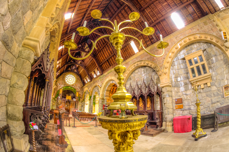 Argyll, Scottish highlands, United Kingdom - June 1, 2015: close op the golden candelabrum in the chancel hall of Saint Conans Kirk gothic church. Nave with benches on background. Editorial