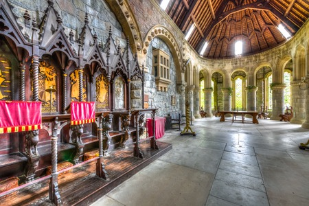Argyll, Scottish highlands, United Kingdom - June 1, 2015: wooden chairs in the chancel hall of Saint Conans Kirk gothic church. Marble colonnade and main altar on background. Editorial