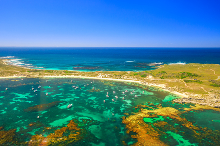 Aerial view of Narrow Neck, Rocky Bay beach and Strickland Bay in Rottnest Island, Australia. Scenic flight over famous tourist destination of Western Australia. Indian Ocean with reef. Copy space.
