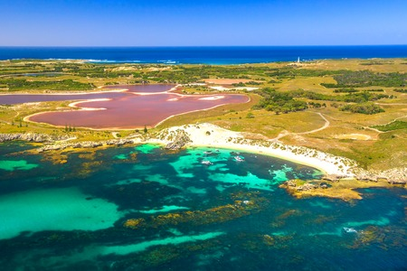 Aerial view of Pink lake and coastline of Rottnest Island in Australia. Scenic flight over famous tourist destination of Western Australia. Rottnest Island is located near Fremantle and Perth.