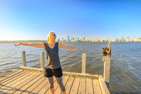 Happy blonde caucasian woman with open arms near an australian darter on a wooden pillar on the Swan River, Perth, Western Australia. Perth city skyline on blurred background.