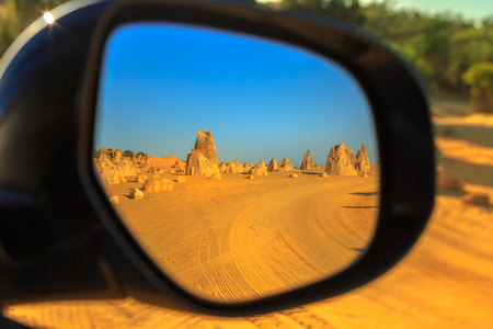 Dirt road of Pinnacles Desert Drive reflecting in the rearview mirror of a tourist car, Nambung National Park, Western Australia. Discovery and adventure tourism concept. Stock Photo