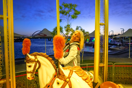 Happy blonde caucasian woman riding on white horse of carousel, at Esplanade in Perth, Western Australia. Elizabeth Quay by night. Leisure and recreational concept.