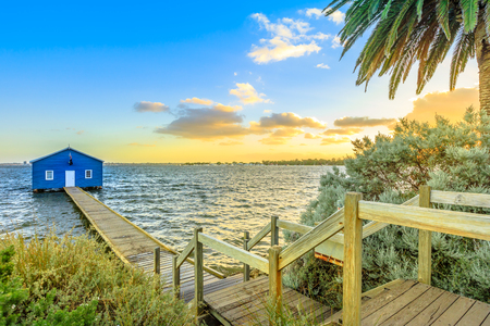 The iconic landscape of Blue Boat House with wooden jetty on Swan River at sunset light. One of the most photographed locations in Perth, Western Australia, near Kings Park.