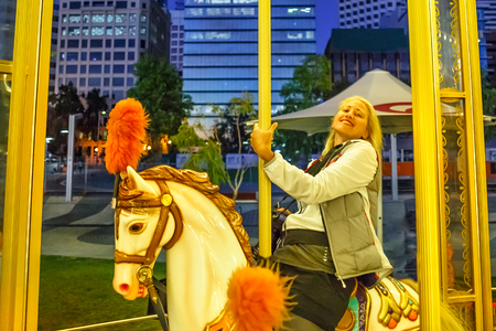 Carefree blonde caucasian woman amuses on white horse of elizabeth quay carousel in Perth, Western Australia. Perth skyline on background. Elizabeth Quay by night. Leisure and recreational concept.