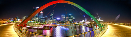 Panorama of coloful arcade and illuminated walkway of Elizabeth Quay Bridge by night at Elizabeth Quay Marina in Perth, Western Australia. Central business district reflecting on Swan River.