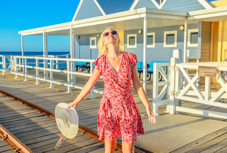 Carefree blonde woman enjoys the sunset light on famous Busselton wooden jetty in Busselton, Western Australia