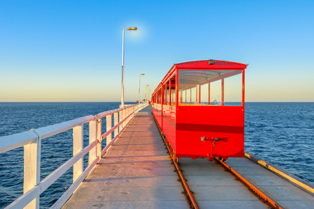 View from behind of vintage red train illuminated by sunset light, going on Jetty Busselton tracks in Busselton town, WA. Busselton Jetty is the longest wooden pier in the world and iconic place. Stock Photo