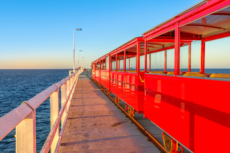 Perspective view of vintage red electric train going on Jetty Busselton tracks in Busselton, Western Australia. Famous place at sunset light. Busselton Jetty is the longest wooden pier in the world.