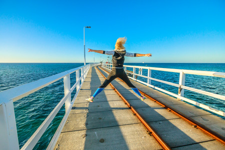 Carefree young sporty woman jumping at Busselton jetty in Busselton, Western Australia. Happy female jumper over iconic wooden pier in WA. Australia travel and freedom concept. Copy space.
