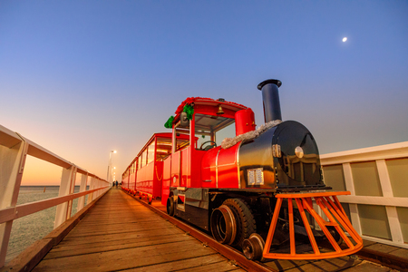 Perspective view of Busselton jetty train in Busselton, Western Australia at blue hour. Scenic landscape of famous landmark at sunset. Busselton jetty is the longest wooden pier in the world.