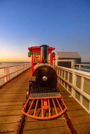 Front view of steam vintage train on Busselton jetty , Busselton town in Western Australia at sunset light. Scenic iconic famous place. Busselton jetty is the longest wooden pier in the world. Stock Photo