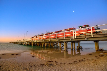 Scenic landscape of Busselton train on Busselton jetty in Busselton Beach, Western Australia, reflected in the sea. Busselton Jetty is the longest wooden pier in the world. Blue hour shot. Stock Photo