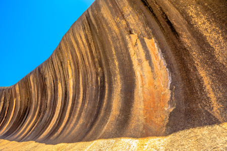 Golden colors of Wave Rock a rock formation that is shaped like a tall ocean wave, Hyden, Western Australia. Wave Rock is part of Hyden Rock in Hyden Wildlife Park. Blue sky. Perspective view. Stock Photo
