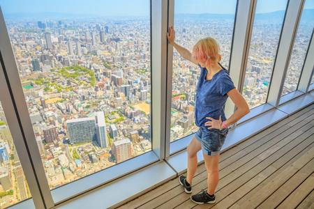 Aerial view of Osaka skyline in Japan. Travel and tourism asia concept. Young caucasian tourist girl looking Osaka cityscape from the observation deck.