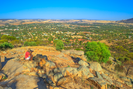 Australia travel discovery concept. Woman photographer take a picture from the summit of Mount Brown. Female with professional camera in York lookout, a popular place in Avon Valley, Western Australia