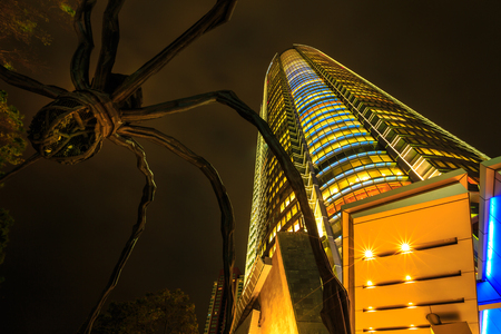 Tokyo, Japan - April 20, 2017: low angle view of Mori Tower and Maman Spider bronze sculpture illuminated at night inside Roppongi Hills complex in Minato District, Tokyo. Night scene.