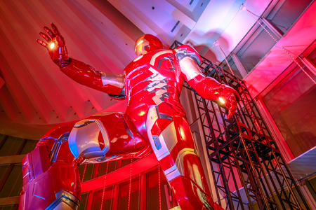 Tokyo, Japan - April 20, 2017: low angle view of gigantic statue of Iron Man of Marvel Age of Heroes Exhibition at Mori Tower in Roppongi Hills complex, from where you can admire Tokyo skyline.