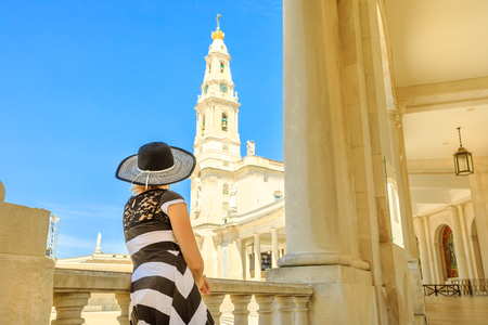 Religious tourism in Portugal. Elegant tourist woman looking at bell tower of Sanctuary of Our Lady of Fatima, Portugal, one of the most important Marian Shrines and pilgrimage locations for Catholics