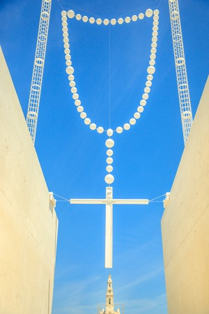 Giant rosary in the blue sky and bell tower of Basilica of Our Lady of Fatima on background. Fatima in Portugal is the site where three Portuguese Shepherd children saw the Virgin Mary of Rosary. Banque d'images