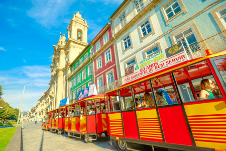 Braga, Portugal - August 12, 2017: red tourist train along Avenida Central alongside Convent of Congregados or Convent of Congregation in urban center of Braga, one of the oldest cities of Portugal