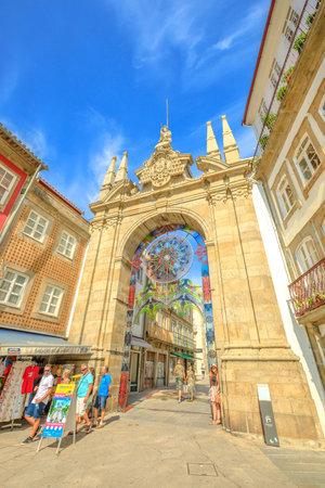 Braga, Portugal - August 12, 2017: front facade of Arco da Porta Nova, looking east along Rua Dom Diogo de Sousa. Arch of the New Gate in Baroque style is part of Braga city walls. Vertical shot.