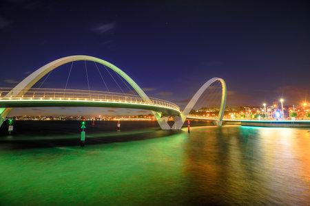 Elizabeth Quay Bridge by night on Swan River at entrance of Elizabeth Quay marina. The arched pedestrian bridge is a tourist attraction in Perth, Western Australia. Copy space. Editorial