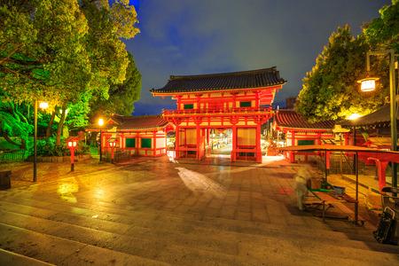 Main gate Ro-mon of Yasaka Shrine illuminated at night on the main street Higashi Oji Dori. The Gion Shrine is one of the most famous shrines in Kyoto between Gion District and Higashiyama District. Фото со стока