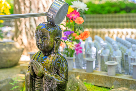 Detail of worshipping at Jizo Statue. Hase-dera Temple in Kamakura, Japan. Japanese culture concept. Standard-Bild - 99364367