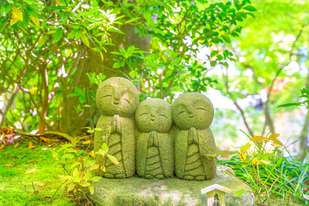 Three statues of Jizo in a foliage blur background. Hase-dera in Kamakura, Japan. Hasedera is one of the largest Buddhist temples in the city within a pilgrimage circuit of the goddess Benzaiten.