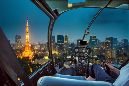 Helicopter flying on Tokyo Skyline at dusk with illuminated Tokyo Tower, icon and landmark of Minato Distric in Tokyo, Japan.